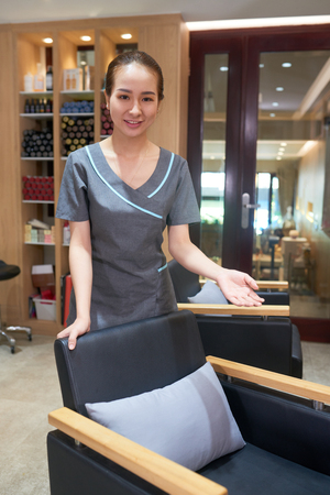 Attractive Asian hairdresser in beauty salon