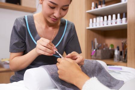 Nail specialist pushing cuticles backwards