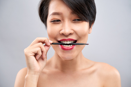 Young woman with lip brush
