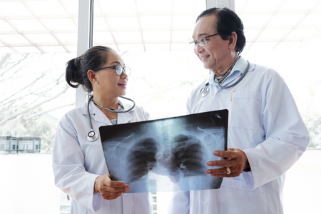 Smiling doctors with x-ray of recovered patient