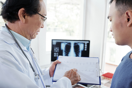 Doctor and patient discussing cardiogram Stock Photo