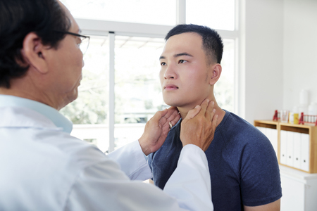 Endocrynologist checking thyroid of patient Zdjęcie Seryjne