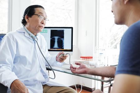 Arzt misst den Blutdruck des Patienten