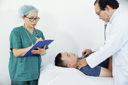 Doctor and nurse examining patient