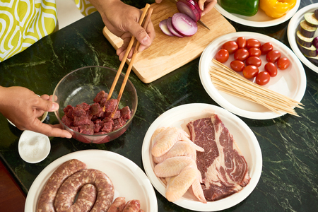 People making sausage and kebab out of various kinds of meat, view from above
