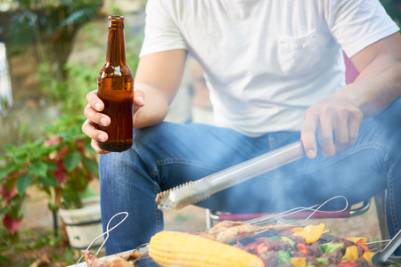 Man drinking beer when cooking meat and vegetables on grill 스톡 콘텐츠
