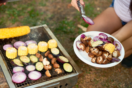 Woman putting cut corn, mushroom, onion and eggplant on grill Stockfoto