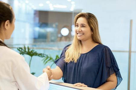 Paciente femenino sonriente estrecharme la mano sobre el doctor Foto de archivo