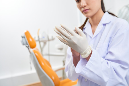 Dentist putting on latex gloves Фото со стока