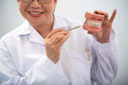 Smiling dentist showing innovative teeth braces 版權商用圖片