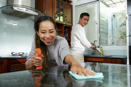 Happy couple cleaning kitchen after dinner
