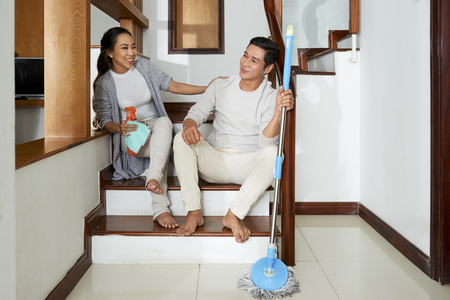Couple resting on steps and yet cleaning apartment