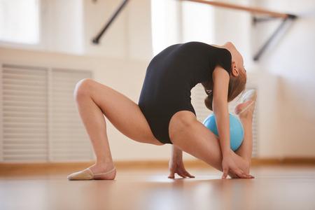 Pełna długość portret elastycznej dziewczyny robi gimnastykę z piłką w studio oświetlonym światłem słonecznym, kopia przestrzeń