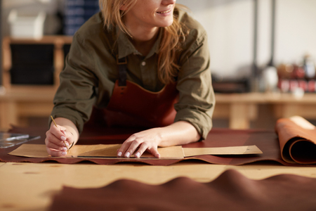 Close up portrait of female artisan working with leather in workshop, copy space Stock fotó