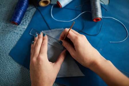 Top view closeup of female hands sewing leather clothes in dressmaking shop, copy space Stock Photo - 121725082