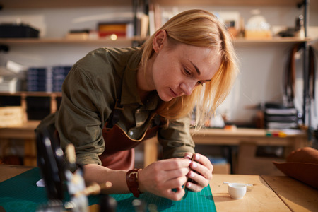 Warm toned portrait of female artisan making leather bag in leatherworking atelier, copy space