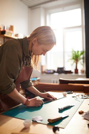Female Artisan in Sunlit Shop Stock fotó