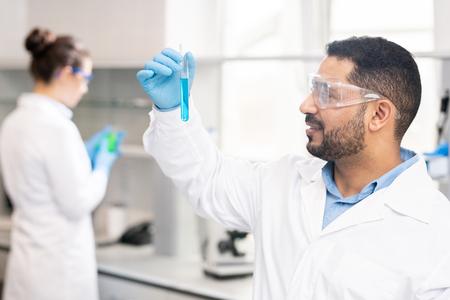Moderner Chemiker, der die Farbe der Flüssigkeit überprüft
