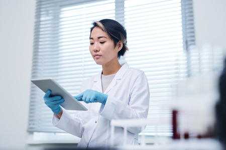 Busy Asian laboratory specialist working with data