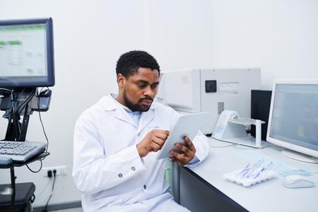 Black medical scientist analyzing data on tablet