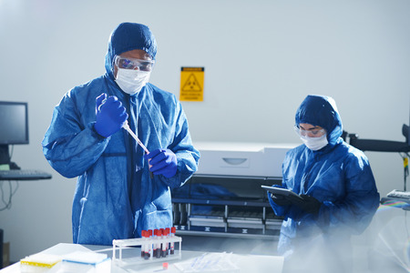 Virologist in protection workwear busy with samples