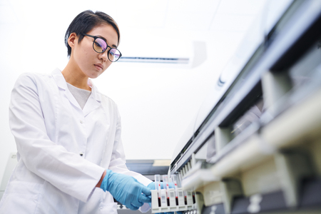 Asian laboratory employee placing blood samples into machine Standard-Bild