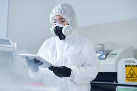 Biologist in protective costume using tablet