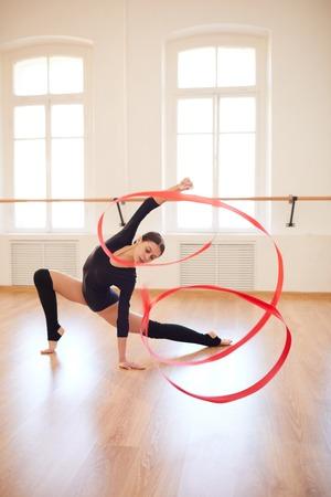 Slim girl dancing with gymnastic ribbon