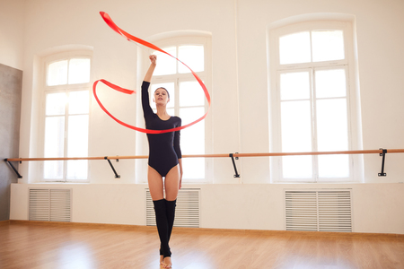 Elegant girl performing rhythmic gymnastics in studio