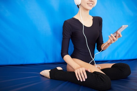 Positive gymnast listening to music in headphones
