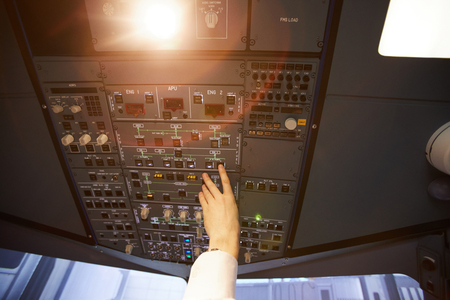 Pilot pushing buttons in aircraft