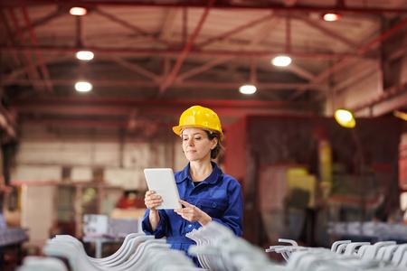 Mujer sonriente con tableta digital en la fábrica. Foto de archivo