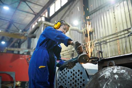 Kiesige Frau beim Schneiden von Metall Standard-Bild