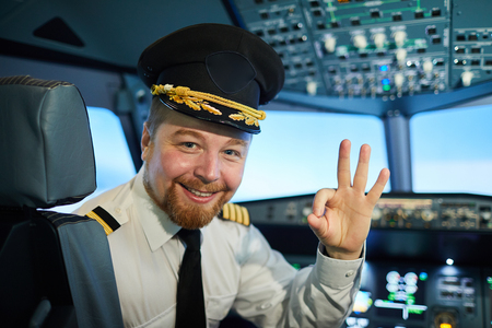 Positive captain of passengers plane showing ok sign Stock Photo