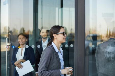 Business people walking through revolving door
