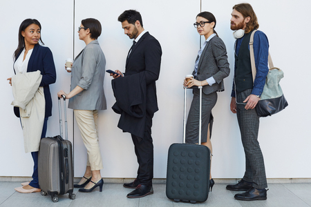 Multi-ethnic people with luggage standing in line