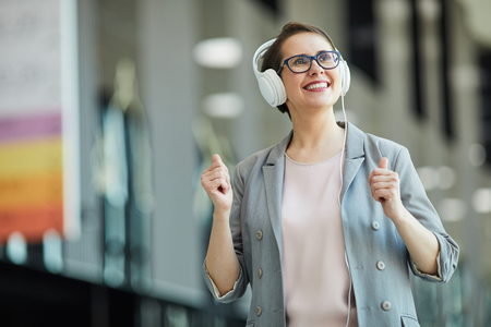 Happy middle-aged lady listening to music