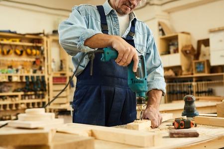 Unerkennbarer Zimmermann, der Holz bohrt