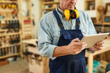 Senior Carpenter using Tablet