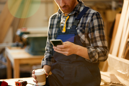 Mid section portrait of modern carpenter using smartphone during coffee break in joinery, copy space Banco de Imagens