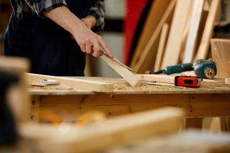 Gros plan d'un charpentier méconnaissable sculptant du bois tout en travaillant dans la menuiserie éclairée par la lumière du soleil, espace de copie