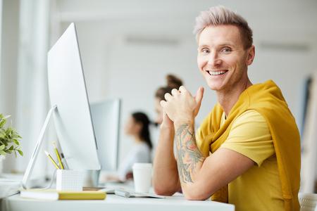 Tattooed Man Enjoying Work in Office
