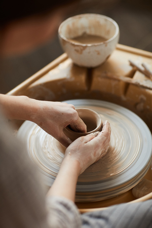 Close-up of unrecognizable woman with smeared hands shaping clay on pottery wheel while making vase with love Stok Fotoğraf