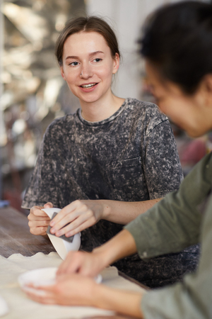 Cheerful young craftswomen in casual tshirts sitting at desk and talking while working with clay crockery in workshop Stock Photo - 123550200