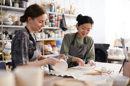 Positive attractive young multi-ethnic women in aprons sitting at table with craft tools and processing dishes with sandpapers in workshop
