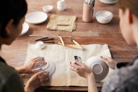 Rear view of unrecognizable craftswomen sitting at old wooden table and polishing clay dishes with sandpapers in workshop