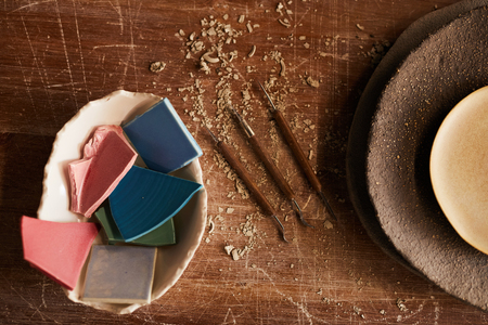 High angle view of handmade ceramics pieces in bowl, stack of textured plated and various craft tools for moulding
