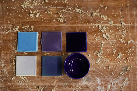 High angle view of ceramic samples in blue shadows and purple bowl placed on dirty scratched table with clay dust