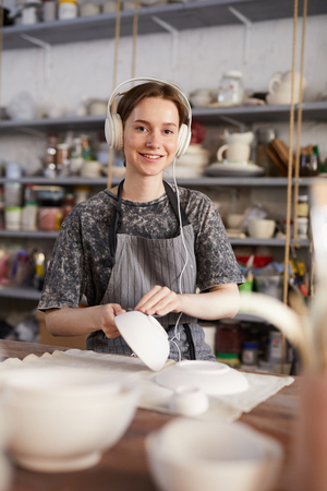 Happy potter checking crockery in workshop Stock Photo - 123550245