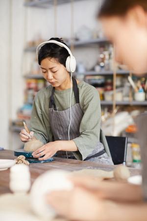 Asian woman shaping bottom of bowl